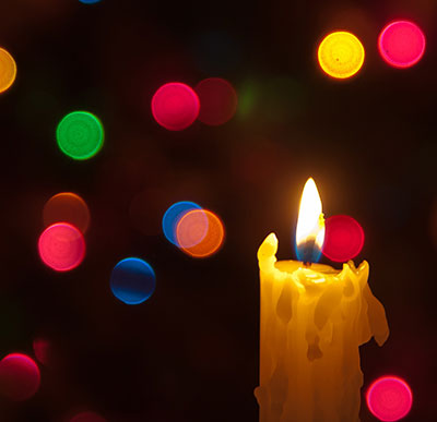 candle in front of Christmas tree lights, photo by Flickr user LenDog64